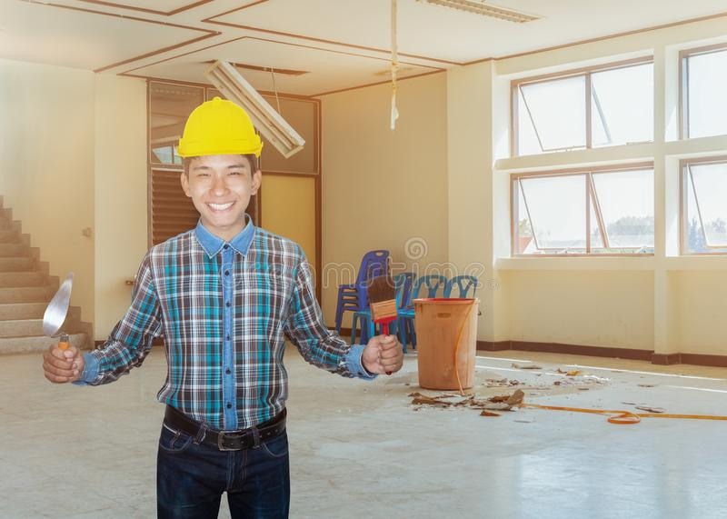 Engineer smile with hand holding triangle trowel and paint brush. in employment repair water leak drop interior office building royalty free stock photos