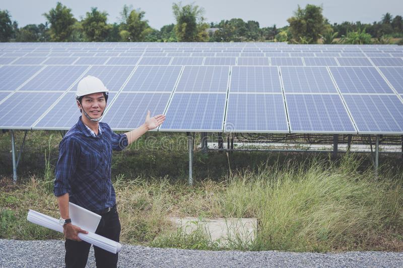 Engineer in solar power plant working on installing solar panel ; smart operator holding blueprint for installing equipment in stock images