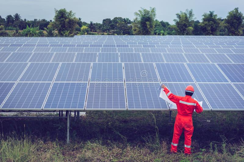 Engineer in solar power plant working on installing solar panel ; smart operator holding blueprint for installing equipment in royalty free stock images