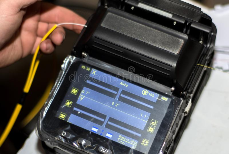 Engineer splicing fiber optic cable with Optical Fiber Fusion Splicer with tool with display stock photography