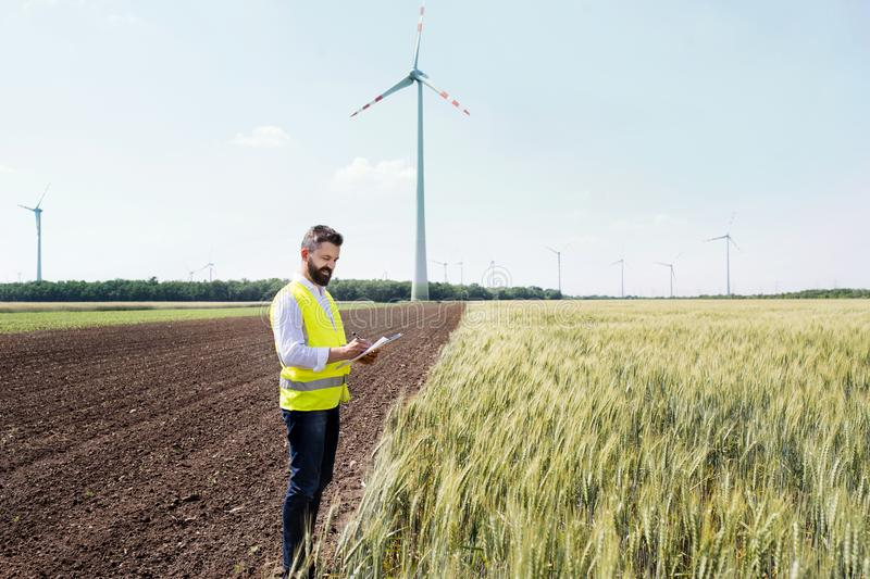 An engineer standing on a field on wind farm, making notes. stock photo