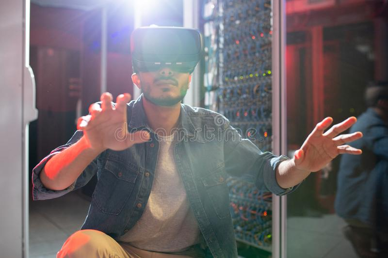 IT engineer studying server systems using VR goggles royalty free stock photos