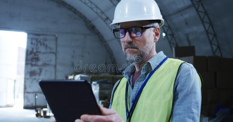 Engineer supervising a robot in a warehouse. Medium shot of engineer supervising a robot in a warehouse royalty free stock images