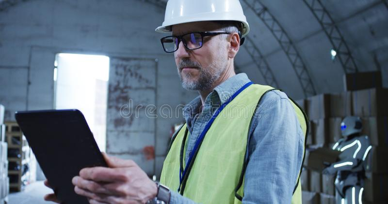Engineer supervising a robot in a warehouse. Medium shot of engineer supervising a robot in a warehouse stock photography