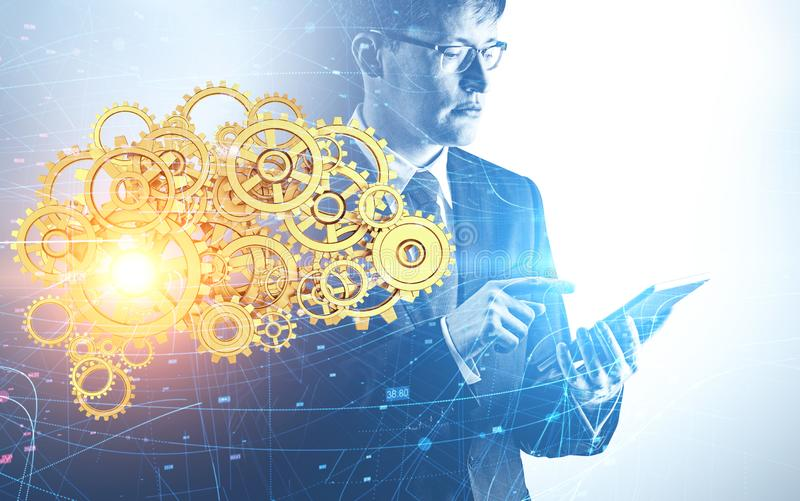 Engineer with tablet, AI brain, machine learning. Serious young engineer working with tablet computer and double exposure of gear brain and network interface royalty free stock photos