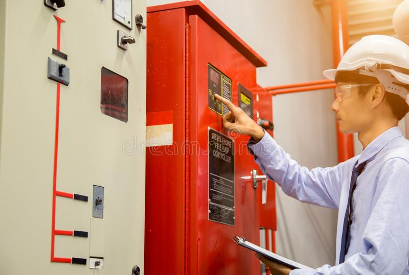 Engineer with tablet check red generator pump for water sprinkler piping and fire alarm control system. Industrial fire control system,Fire Alarm controller stock image