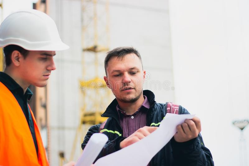 Engineer talking discussing with Architect working with blueprints for architectural plan, sketching a project. royalty free stock photography
