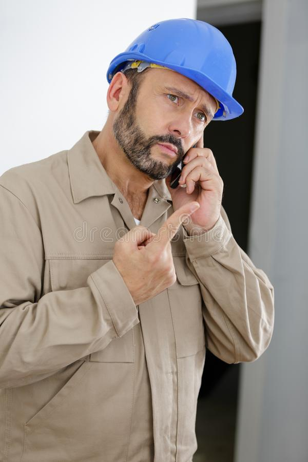 Engineer talking on phone and showing pointing finger up stock image