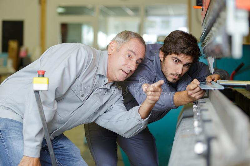Engineer teaching apprentice to use grinding machine royalty free stock photo