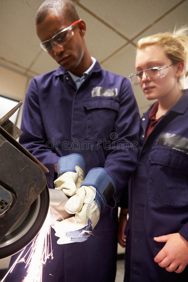 Engineer Teaching Apprentice To Use Grinding Machine. In Factory stock photography
