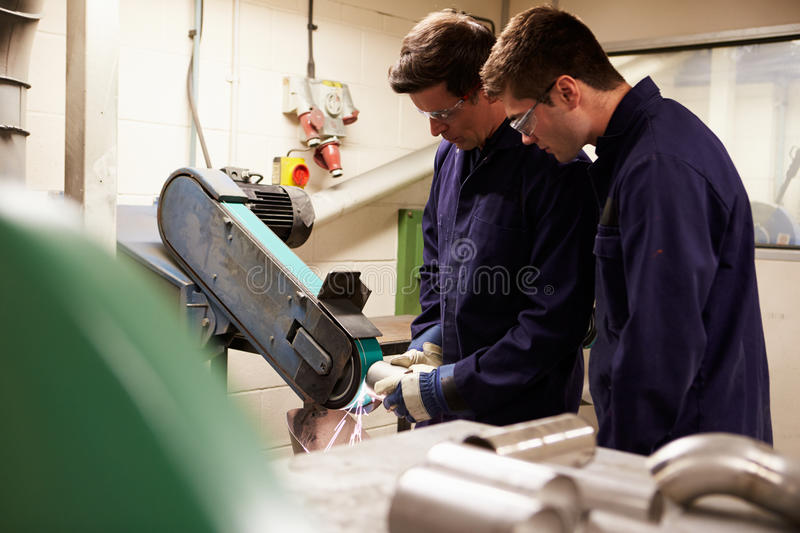 Engineer Teaching Apprentice To Use Grinding Machine. Skilled Engineer Teaching Apprentice To Use Grinding Machine In Factory stock photo