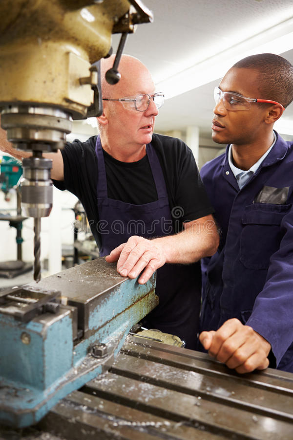Engineer Teaching Apprentice To Use Milling Machine. Looking At Each Other Having A Discussion royalty free stock photo