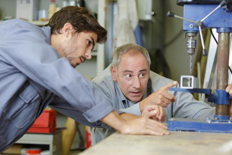 Engineer teaching apprentice to use milling machine stock image