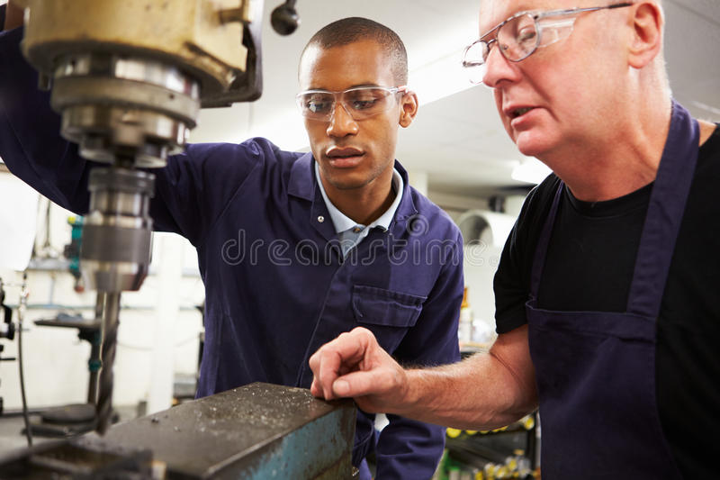 Engineer Teaching Apprentice To Use Milling Machine. Whilst Wearing Uniform And Protective Glasses royalty free stock photos