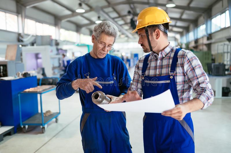 Engineer Teaching Apprentices To Use Computerized cnc metal processing machines royalty free stock image