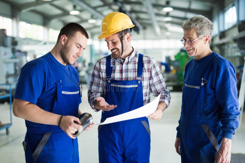 Engineer Teaching Apprentices To Use Computerized cnc metal processing machines royalty free stock photos