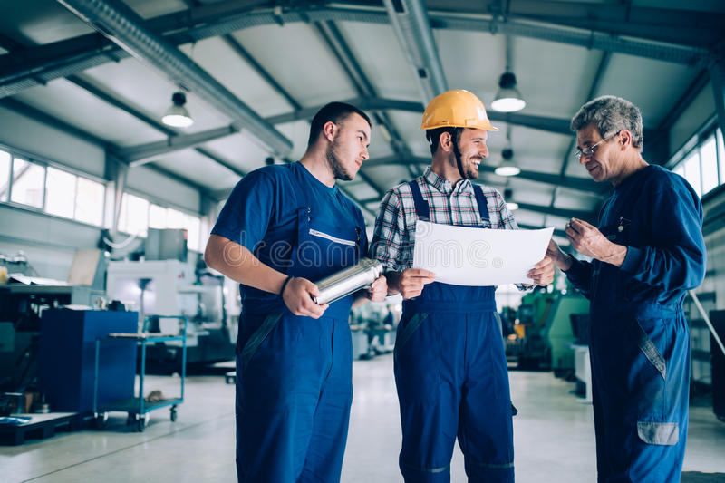 Engineer Teaching Apprentices To Use Computerized cnc metal processing machines royalty free stock photography