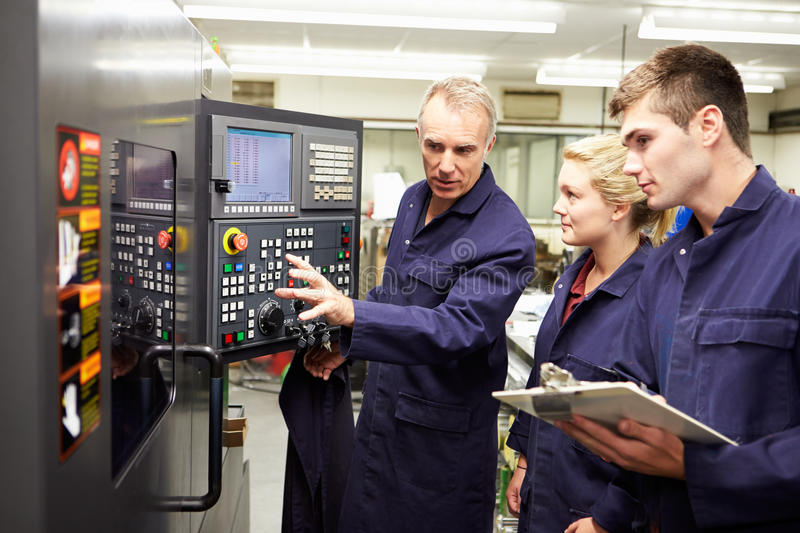 Engineer Teaching Apprentices To Use Computerized Lathe royalty free stock image