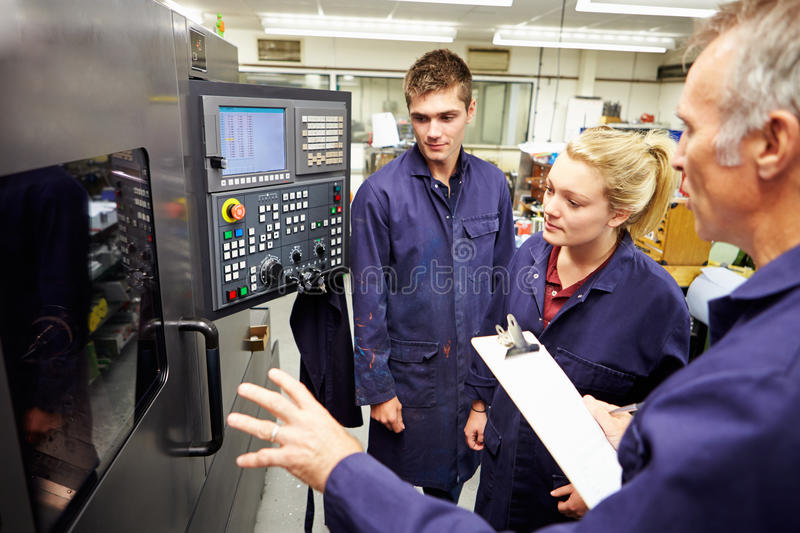 Engineer Teaching Apprentices To Use Computerized Lathe royalty free stock photos