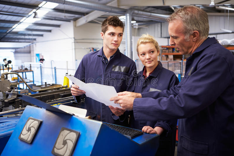 Engineer Teaching Apprentices To Use Tube Bending Machine. Looking At Document stock photo