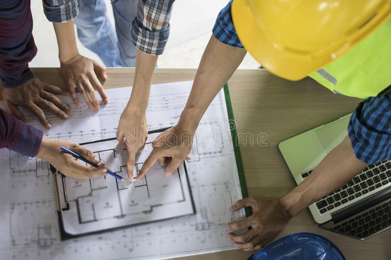 engineer team planning and discussing about construction building on table in working site stock images