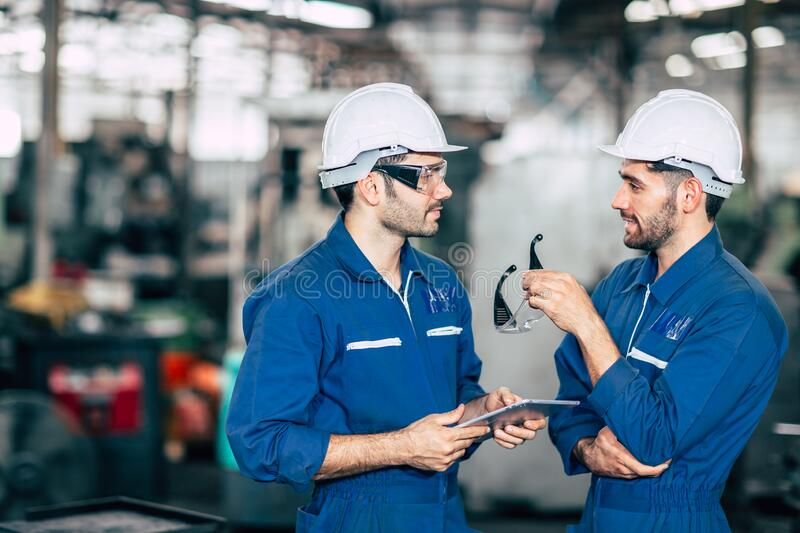 Engineer teamwork cooperate with worker to checking factory machine for safety and talking together.  stock photography