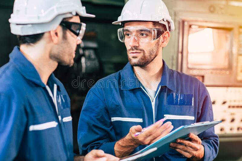 Engineer teamwork cooperate with worker to checking factory machine for safety and talking together.  stock photos