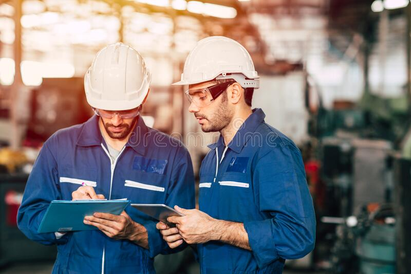 Engineer teamwork cooperate with worker to checking factory machine for safety and talking together.  stock images