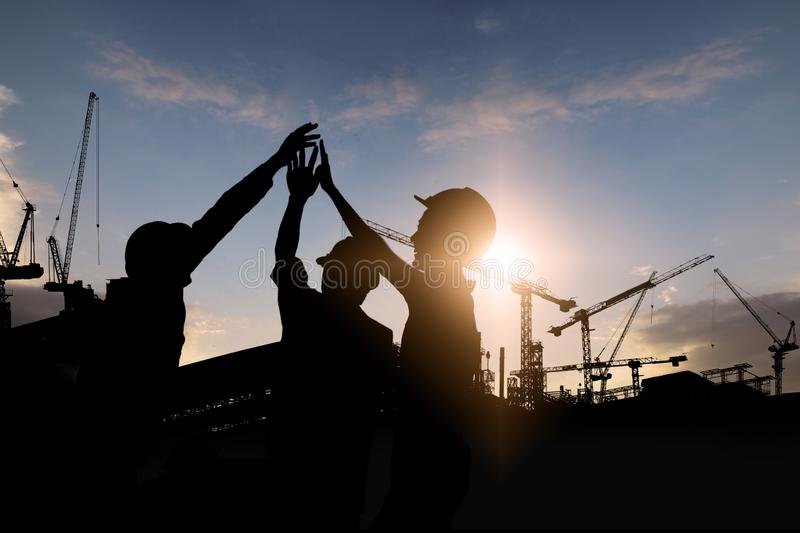 Engineer teamwork, silhouette of construction worker team touching hand together for power at working site stock photography
