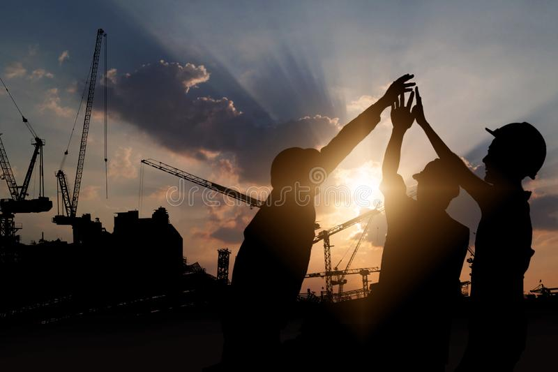 Engineer teamwork, silhouette of construction worker team touching hand together for power at working site stock photos