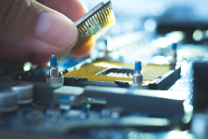 Engineer Technician plug in computer CPU microprocessor to motherboard socket. technology background industry maintenance and rep stock photo