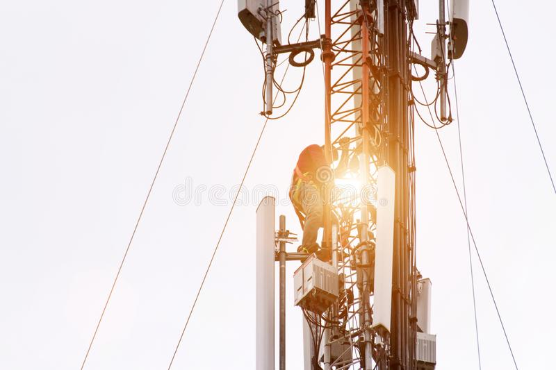 Engineer or Technician working on high tower,Risk work of high work, people are working with safety equipment on tower, stock photography