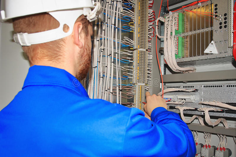 Engineer tests the automation cabinet with industrial equipment controllers royalty free stock image