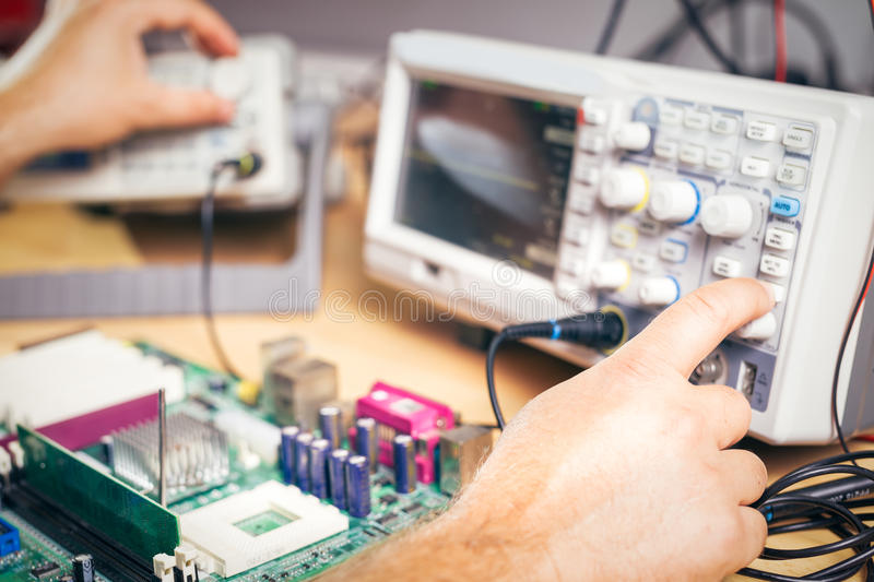 Engineer tests electronic components with oscilloscope in the service center. Engineer tests electronic components with oscilloscope stock photos