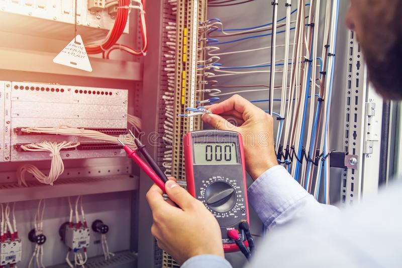 Engineer tests industrial electrical cabinet. Wire in hand of electrician with multimeter. Professional in control panel royalty free stock photography