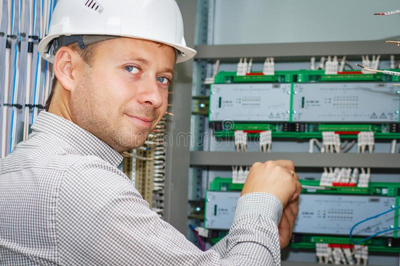 Engineer tests industrial electrical circuits in control terminal box. Electrician adjusts electric equipment in automation panel. stock images