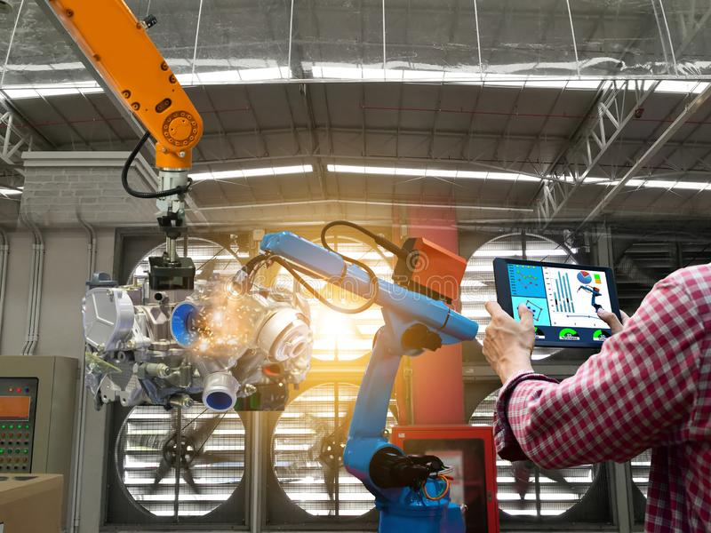 Engineer touch screen control robot the production of factory parts engine manufacturing industry robots. And mechanical arm royalty free stock photos
