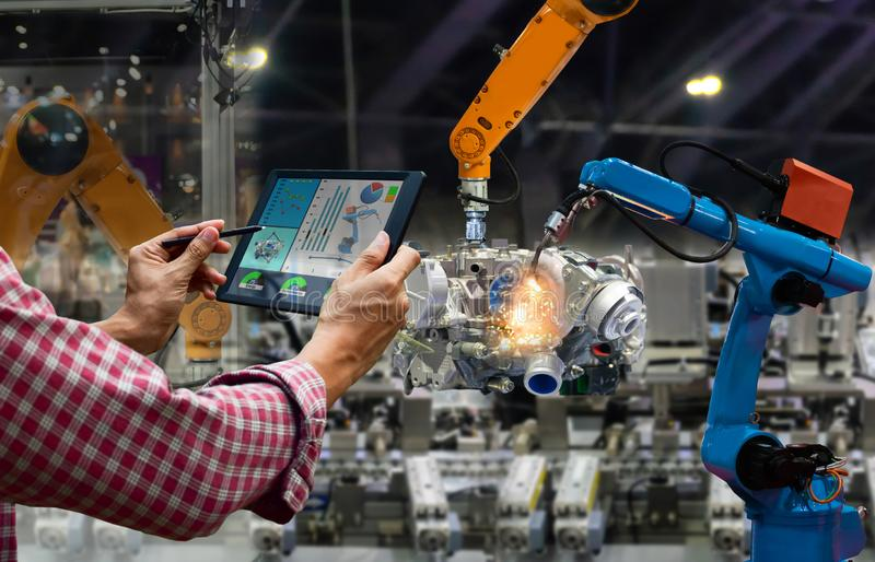 Engineer touch screen control robot the production of factory parts engine manufacturing industry stock photo