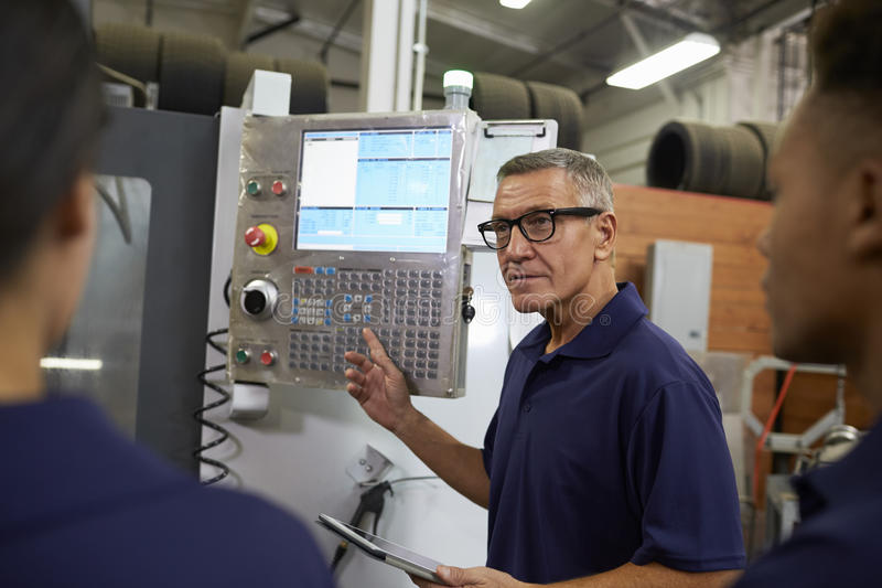Engineer Training Apprentices On CNC Machine stock photo