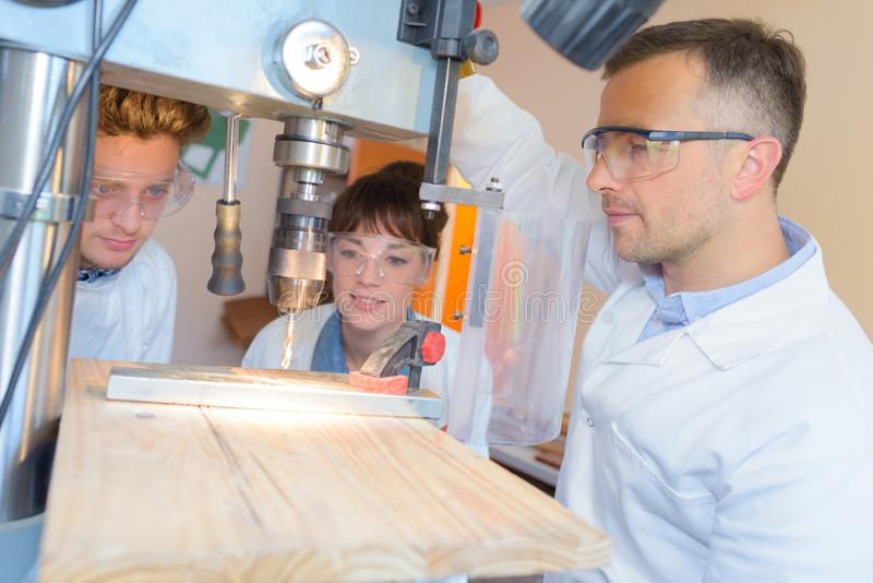 Engineer training female and male apprentice on milling machine. Milling stock photography