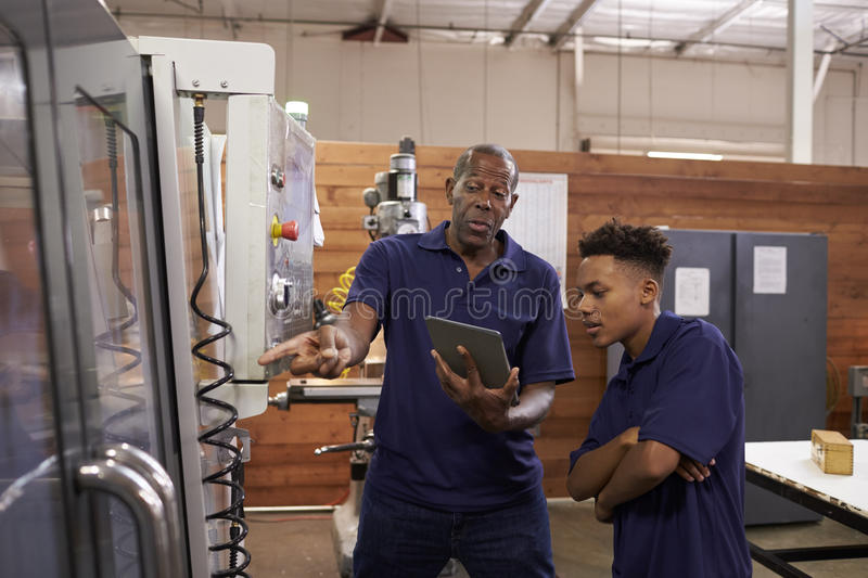 Engineer Training Young Male Apprentice On CNC Machine stock photos