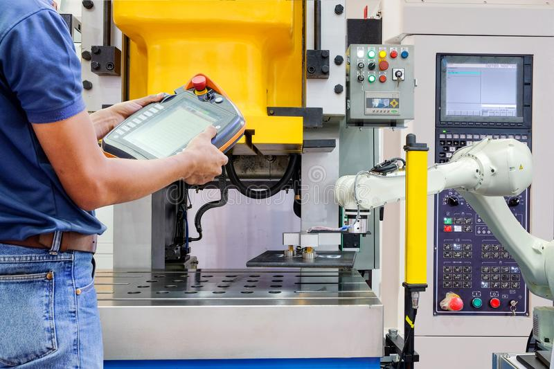 Engineer use wireless remote for control industrial robot working on smart factory stock photography