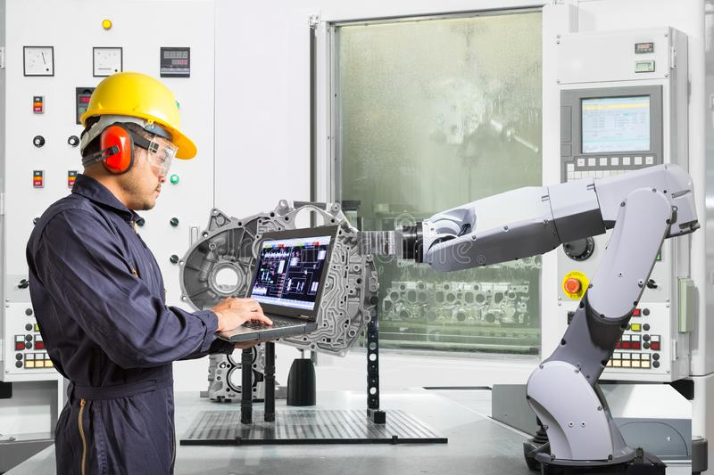 Engineer using laptop computer control automatic robotic hand with CNC machine in automotive industry, Smart factory concept stock image