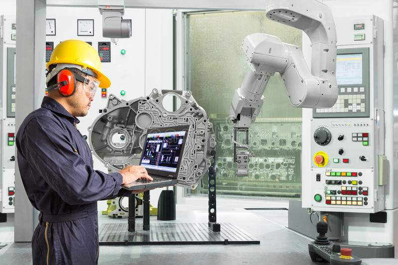 Engineer using laptop computer control automatic robotic hand with CNC machine in automotive industry, Smart factory concept.  stock photography