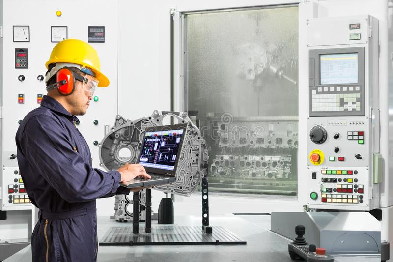 Engineer using laptop computer control automotive CNC machine in automotive industry, Smart factory concept.  royalty free stock photo
