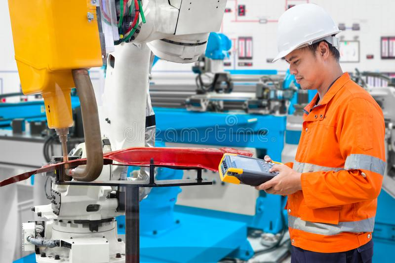 Engineer using laptop computer maintenance robot grip automotive workpiece, Industry 4.0 concept royalty free stock photos