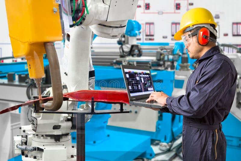 Engineer using laptop computer maintenance robot grip automotive workpiece position, Smart factory concept.  stock images
