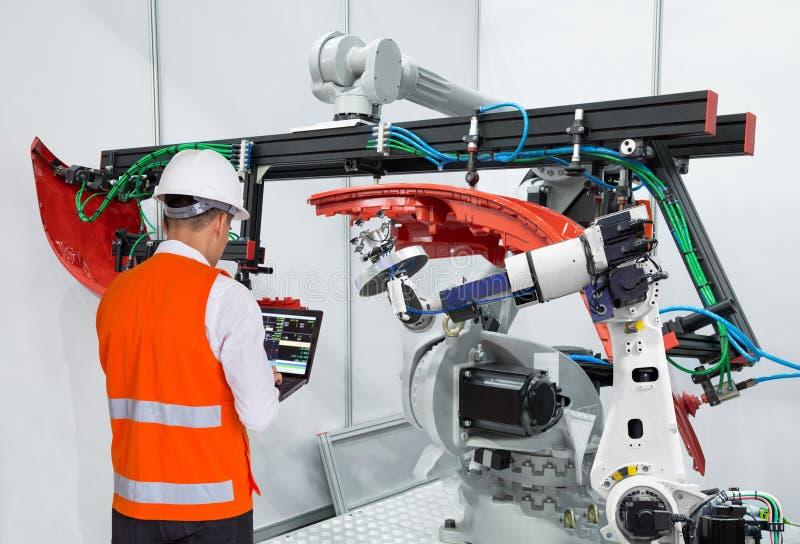 Engineer using laptop computer maintenance robot grip automotive workpiece, Smart factory concept.  stock photo