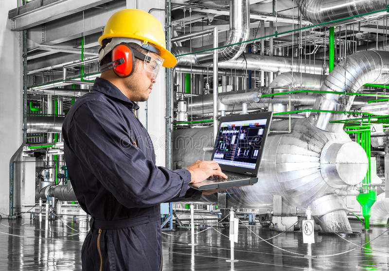 Engineer using laptop computer in thermal power plant factory.  royalty free stock photo