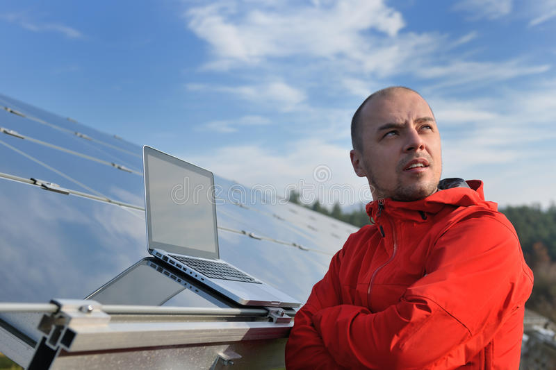 Engineer using laptop at solar panels plant field stock images